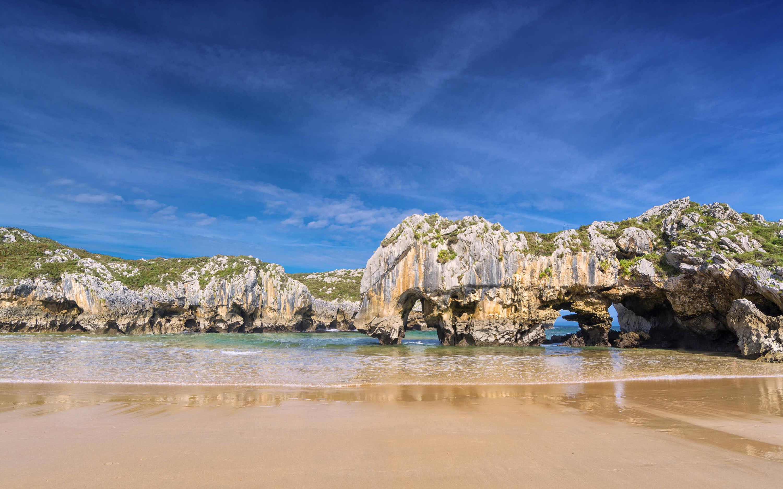 Playa de Cuevas del Mar con su famosa roca en Llanes, Asturias