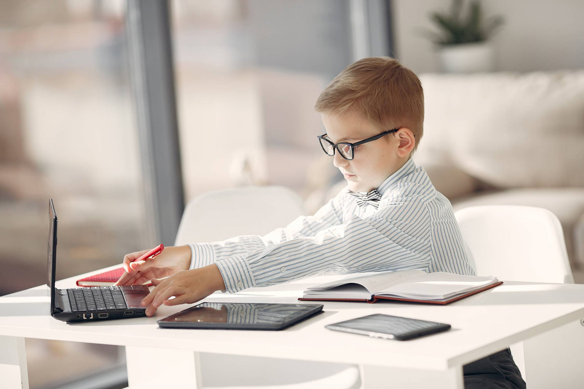 A little boy wearing smart clothes using his dad's computer.