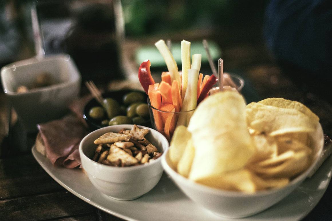 A tray of veggie sticks, olives, chips and crackers.
