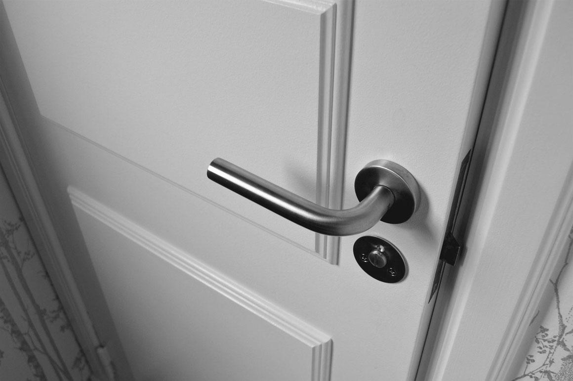 A white closed door with a modern door handle.