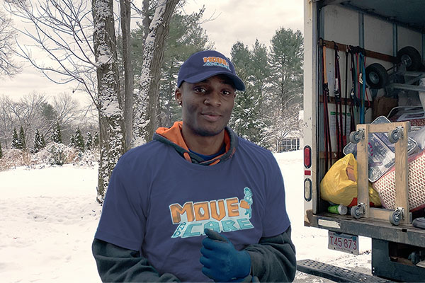 Move and Care team member posing in front of a filled moving truck