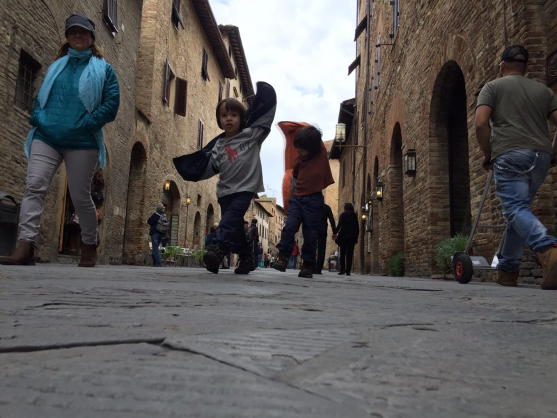 2 kids pretending to be aeroplanes, running down the streets of San Gimignano, Italy