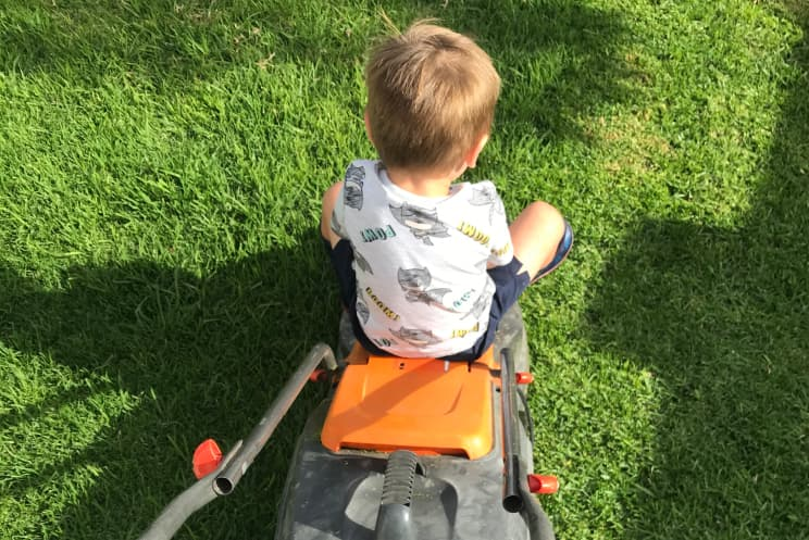 Arlo sitting on the lawnmower while mowing it