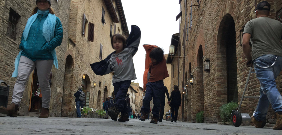Two kids running down an old Italian street pretending to be aeroplanes