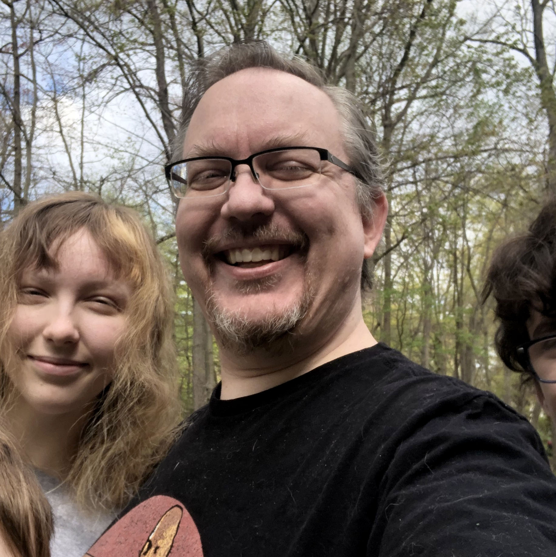 Josh smiling outdoors with two of his children