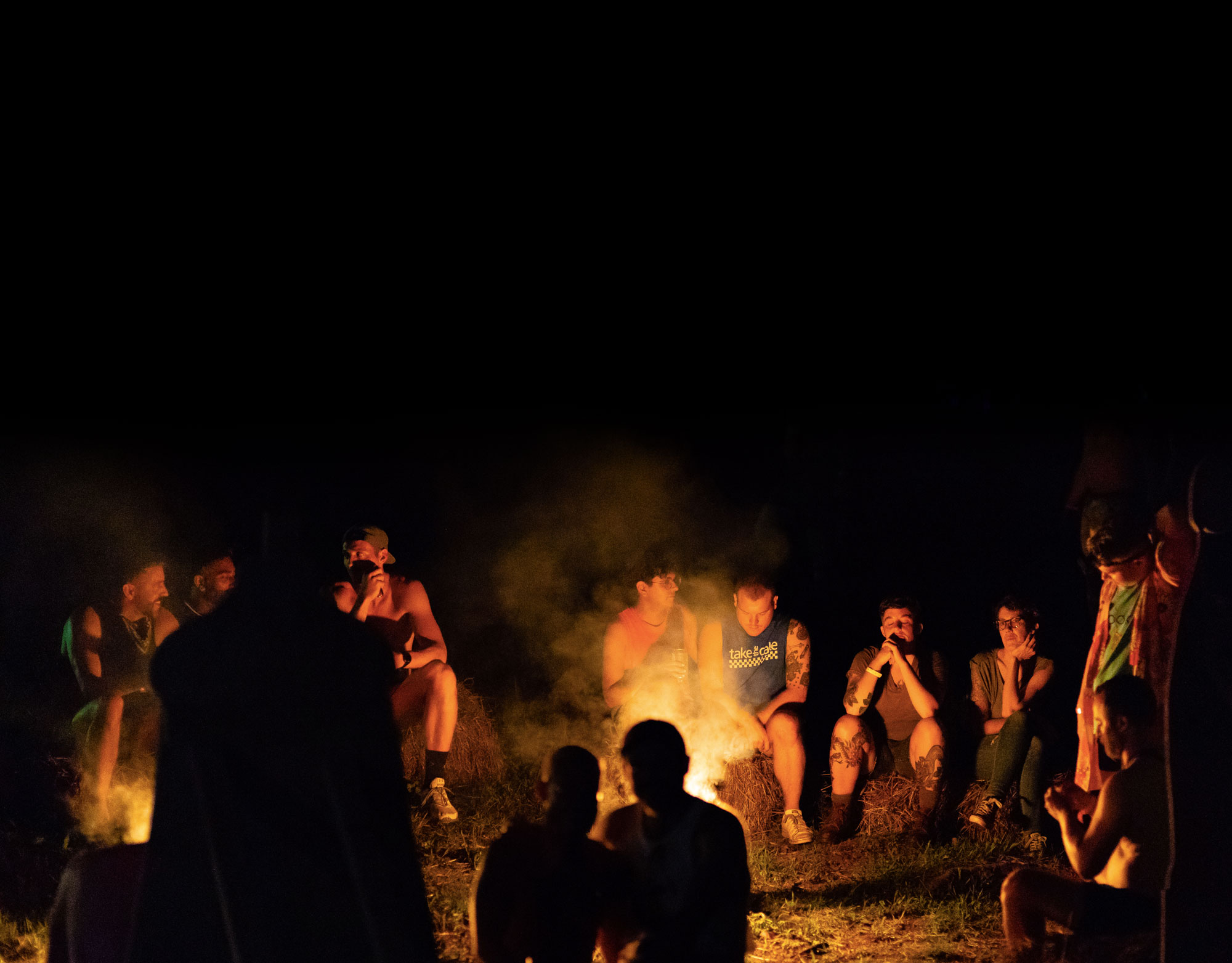 People sitting around a camp fire at night