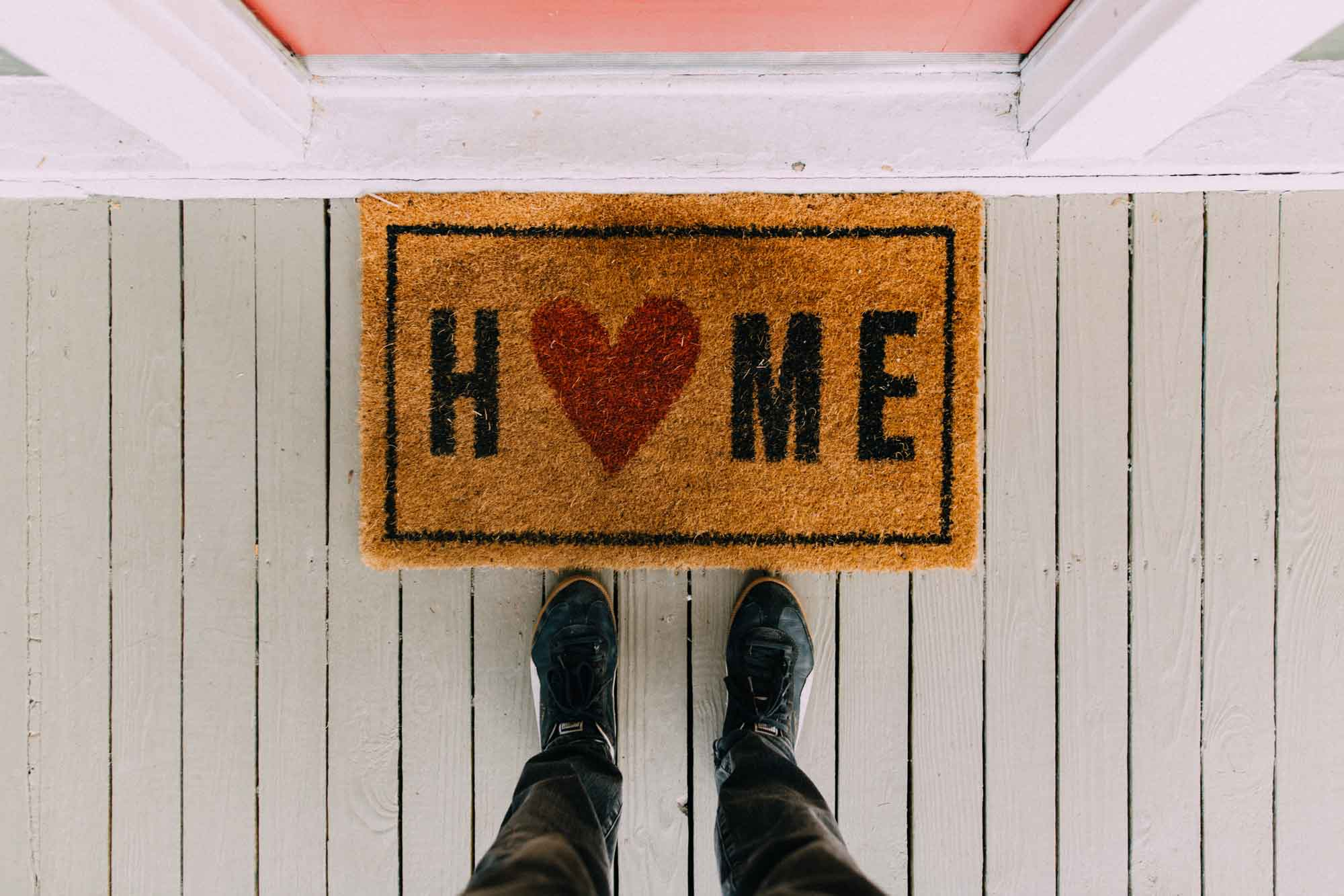 Person standing by doormat that has a home design | Photo by Kelly Lacy from Pexels