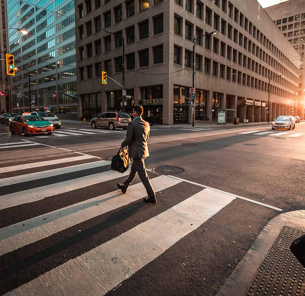 A business man walking on a crosswalk