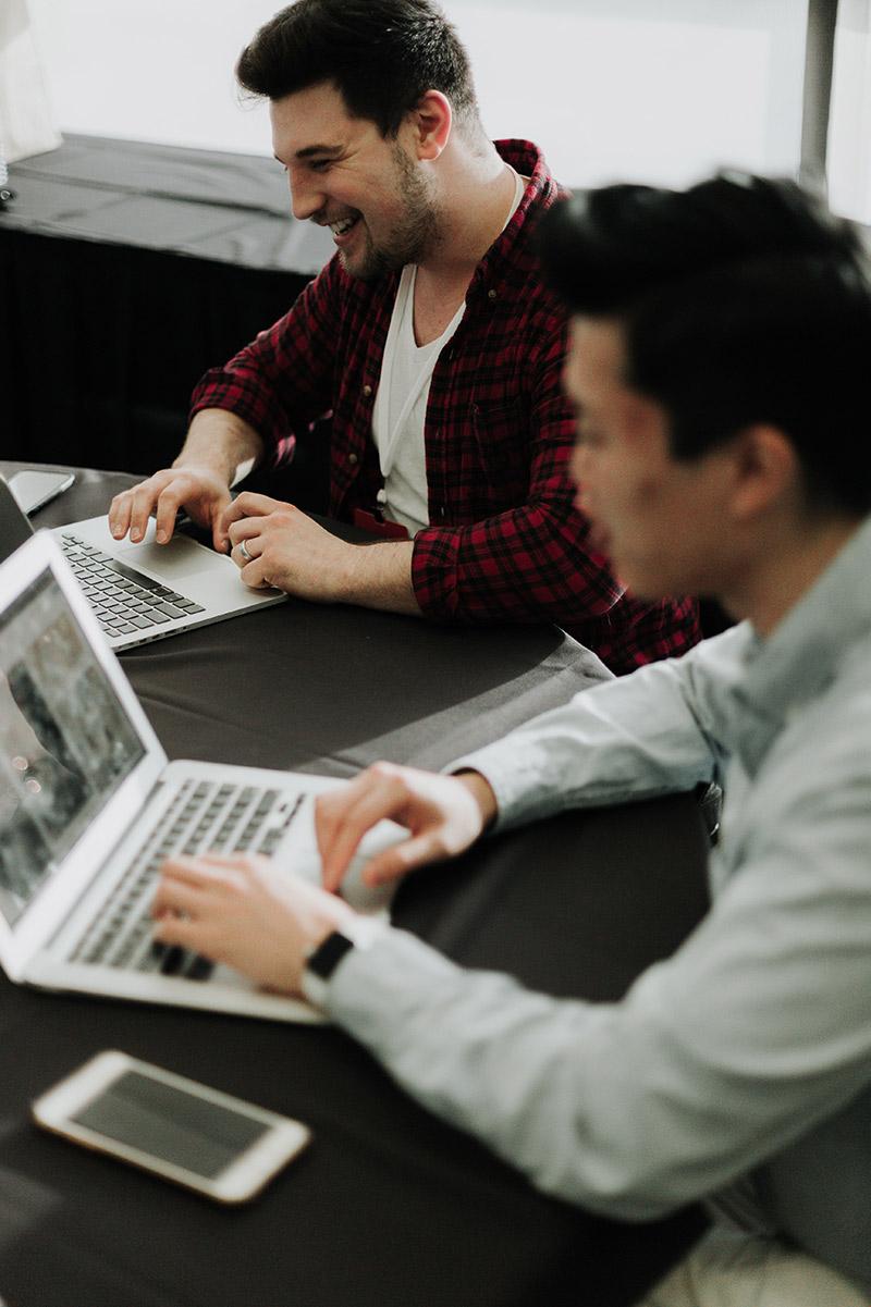 2 men working on laptop