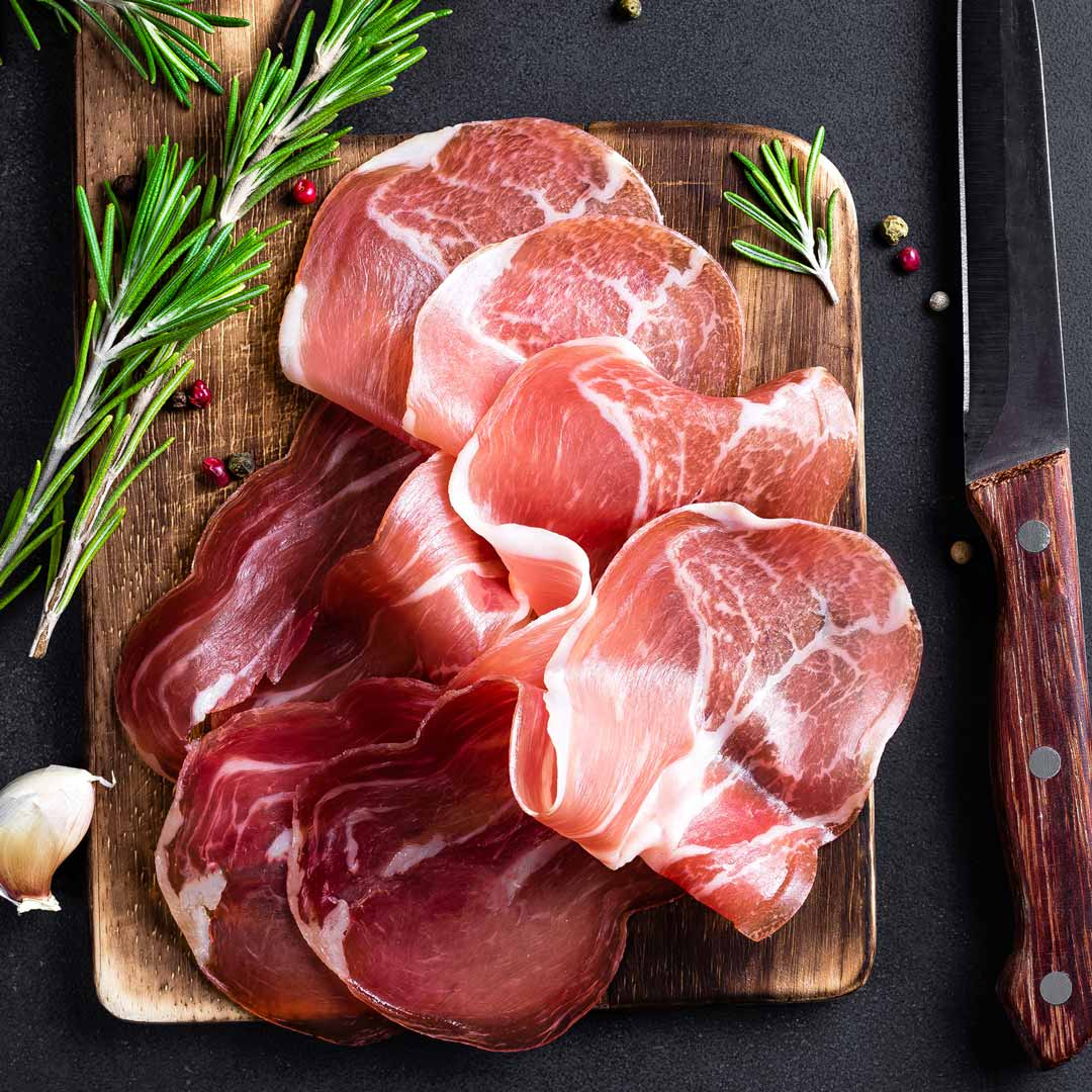 Sliced Prosciutto Presented on display with garnish. Home delivery available on deli and small goods.