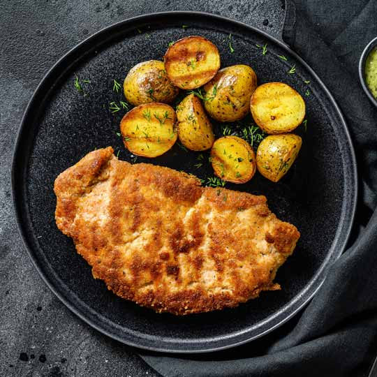 Cooked Chicken Schnitzel on Plate with potatoes