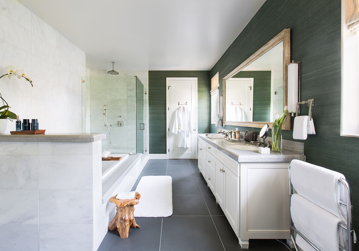 Earthy elements like the vintage, wooden stool and fresh florals brighten up this modern bathroom. White bathroom countertops, cabinets, and bathtub are enhanced by grey tiles and walls of a rich, jade hue.