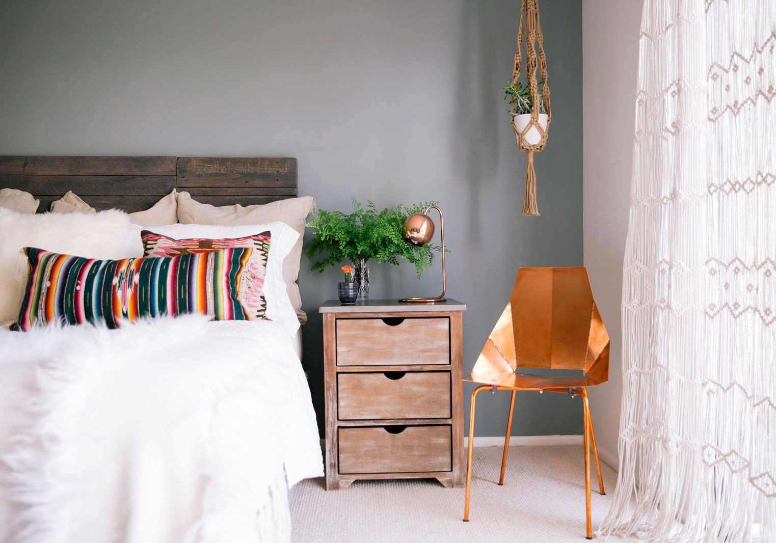 In this bedroom, neutral tones, light and dark distressed wood, botanical accents, and copper chair meet to bring forth effortless vintage chic vibes.