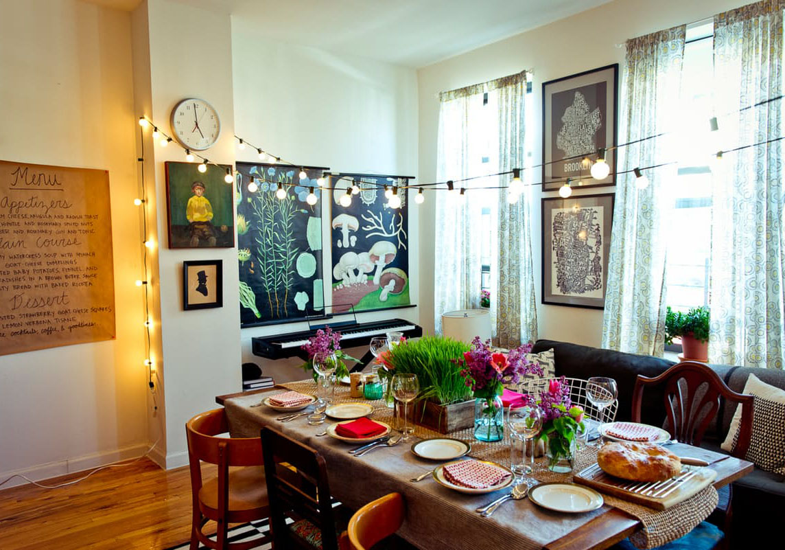 This eclectic dining space is decked out with unique wall art, charming hanging lights, and freshly picked flowers.