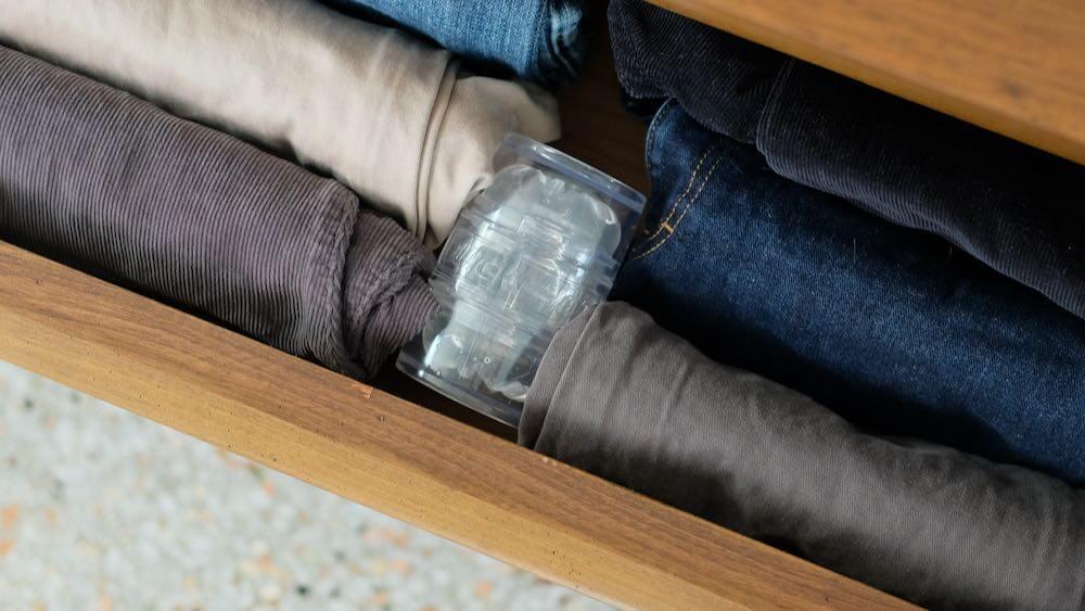 Small dresser drawer with men's pants storing Fleshlight Quickshot