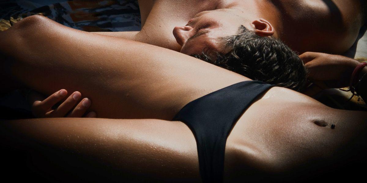 Sexy photo of shirtless man touching woman wearing black panties on hotel bed