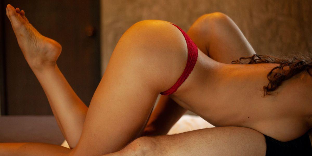 Erotic photo of woman wearing red panties and man in black underwear