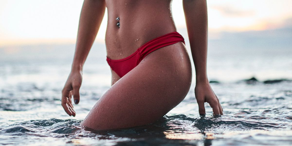 Swimsuit photo of sexy woman wearing red bikini and navel bellybutton ring