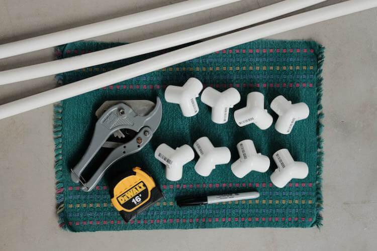 White PVC pipe, PVC cutting tool, Dewalt measuring tape and Sharpie pen