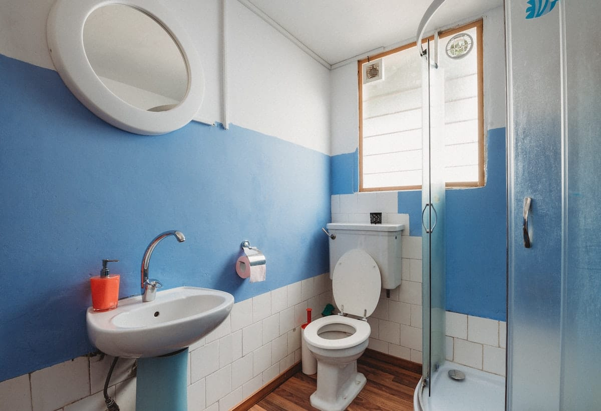 Bathroom with pedestal sink, toilet, and shower