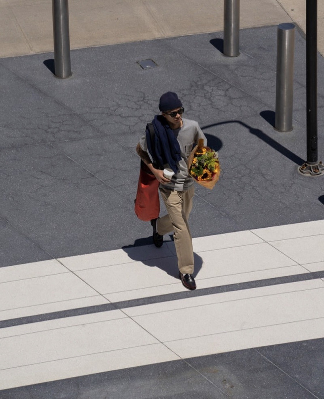 Boy crossing the street with a bouquet of flowers wearing a beanie, cool sunglasses and penny loafers. Image taken from Sebago x One Block Down Spring/Summer 2020 Capsule Editorial.