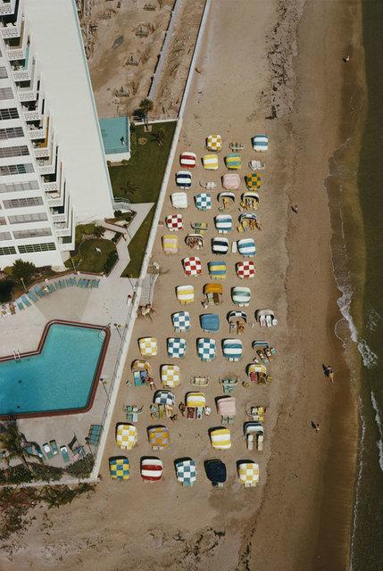 Slim Aarons aerial beach shot. Colorful beach umbrellas.