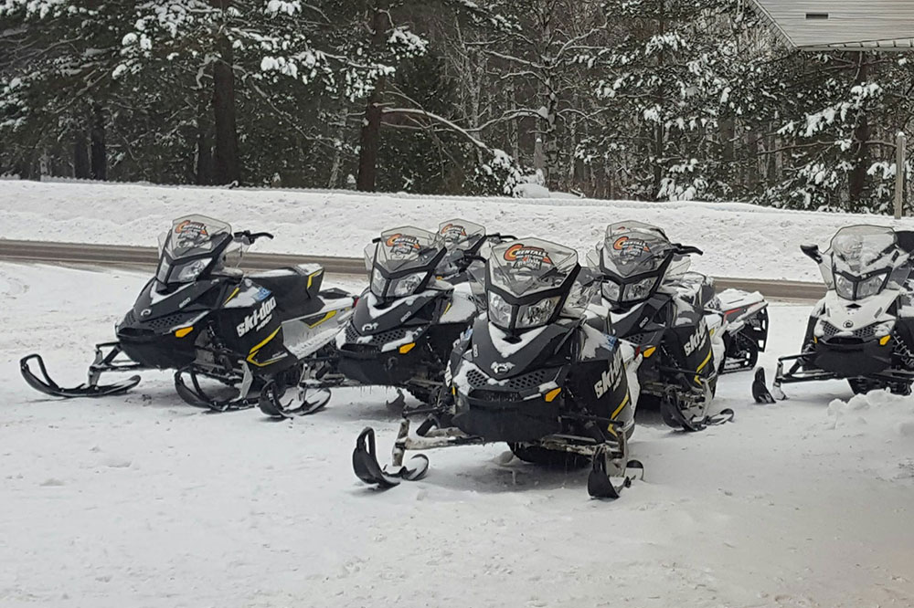 winter scene of snowmobiles for rent at Copper Country Rentals in Calumet MIchigan
