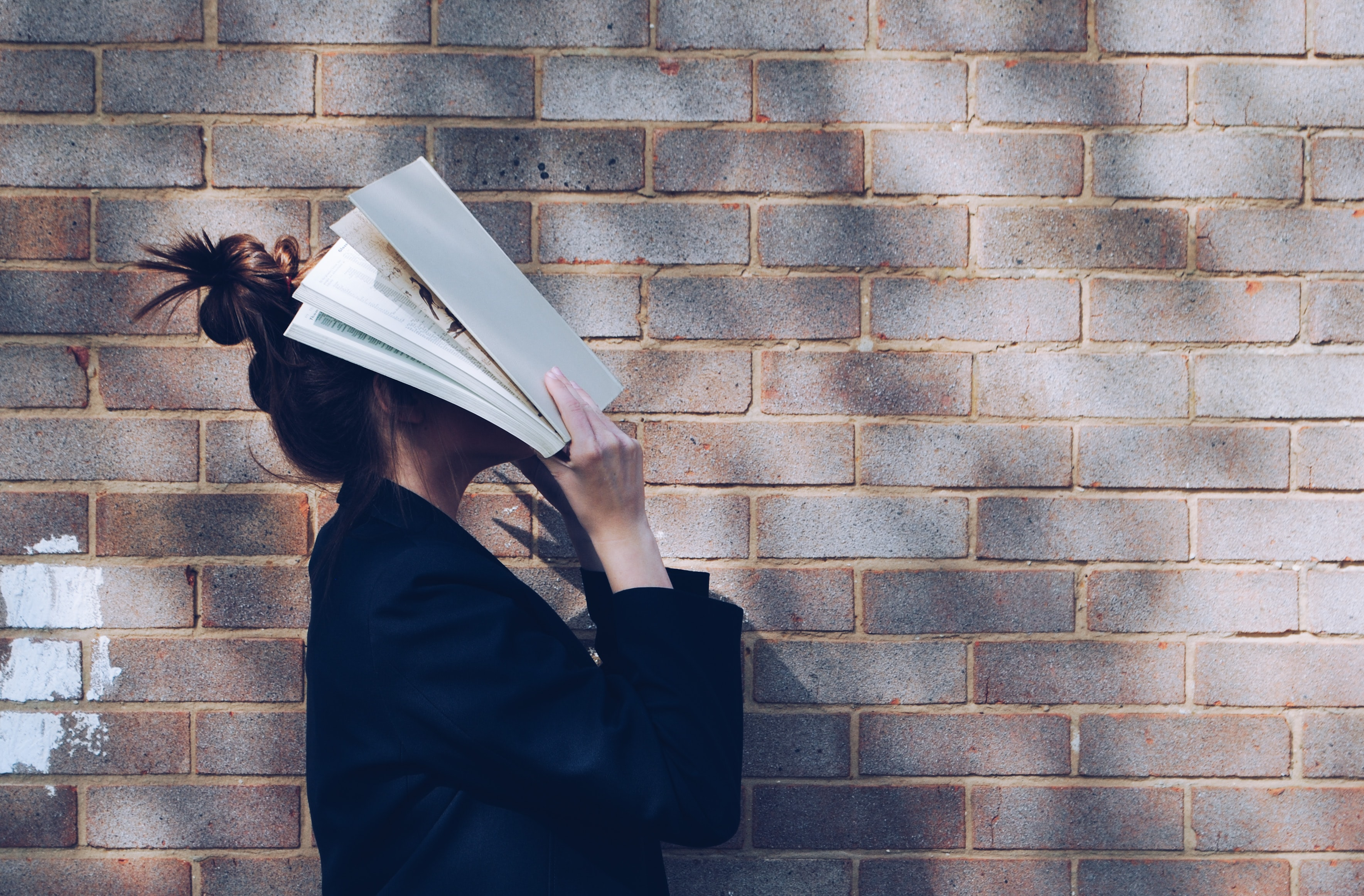 Student with a book on face