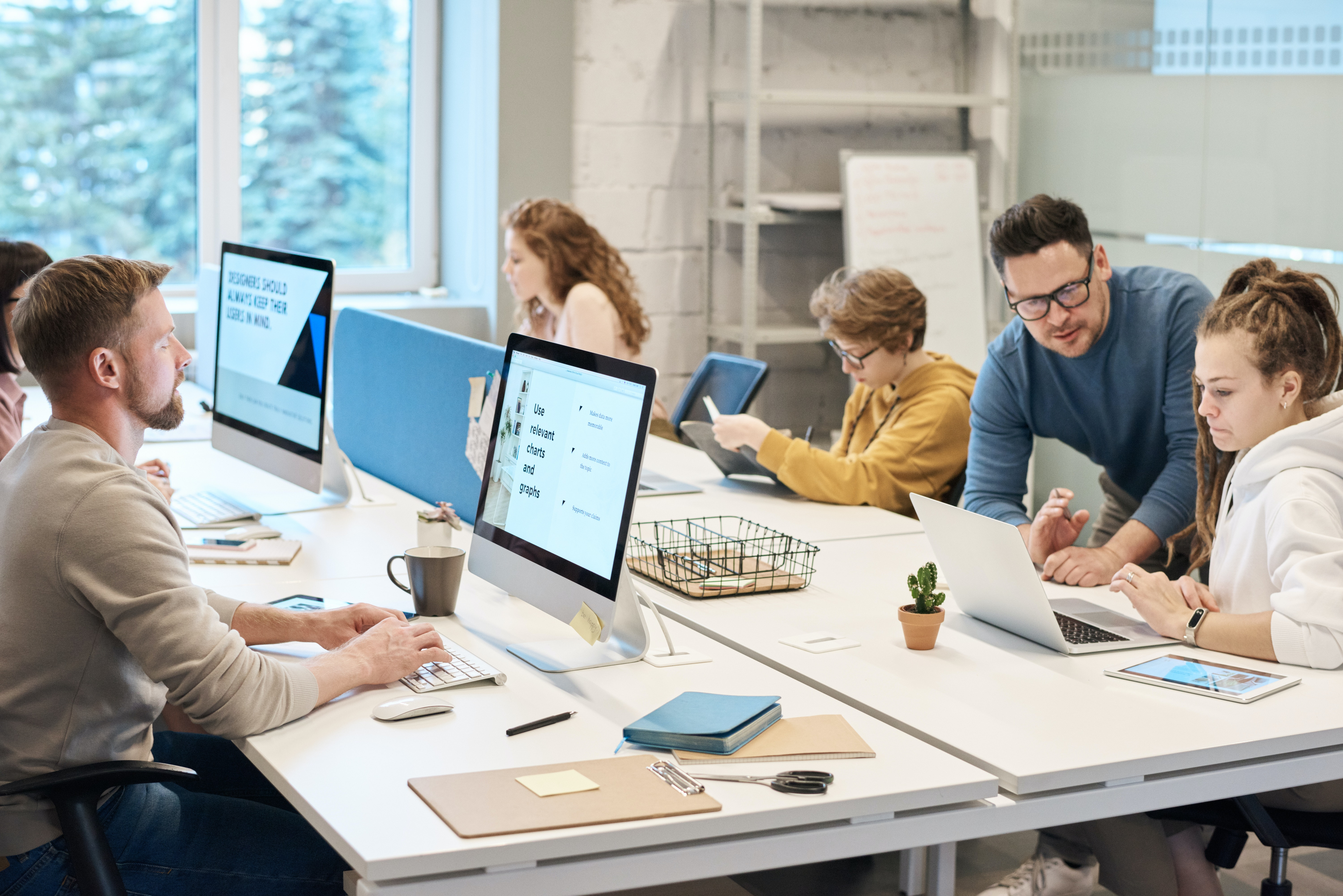 People sitting and talking around an office room computer table