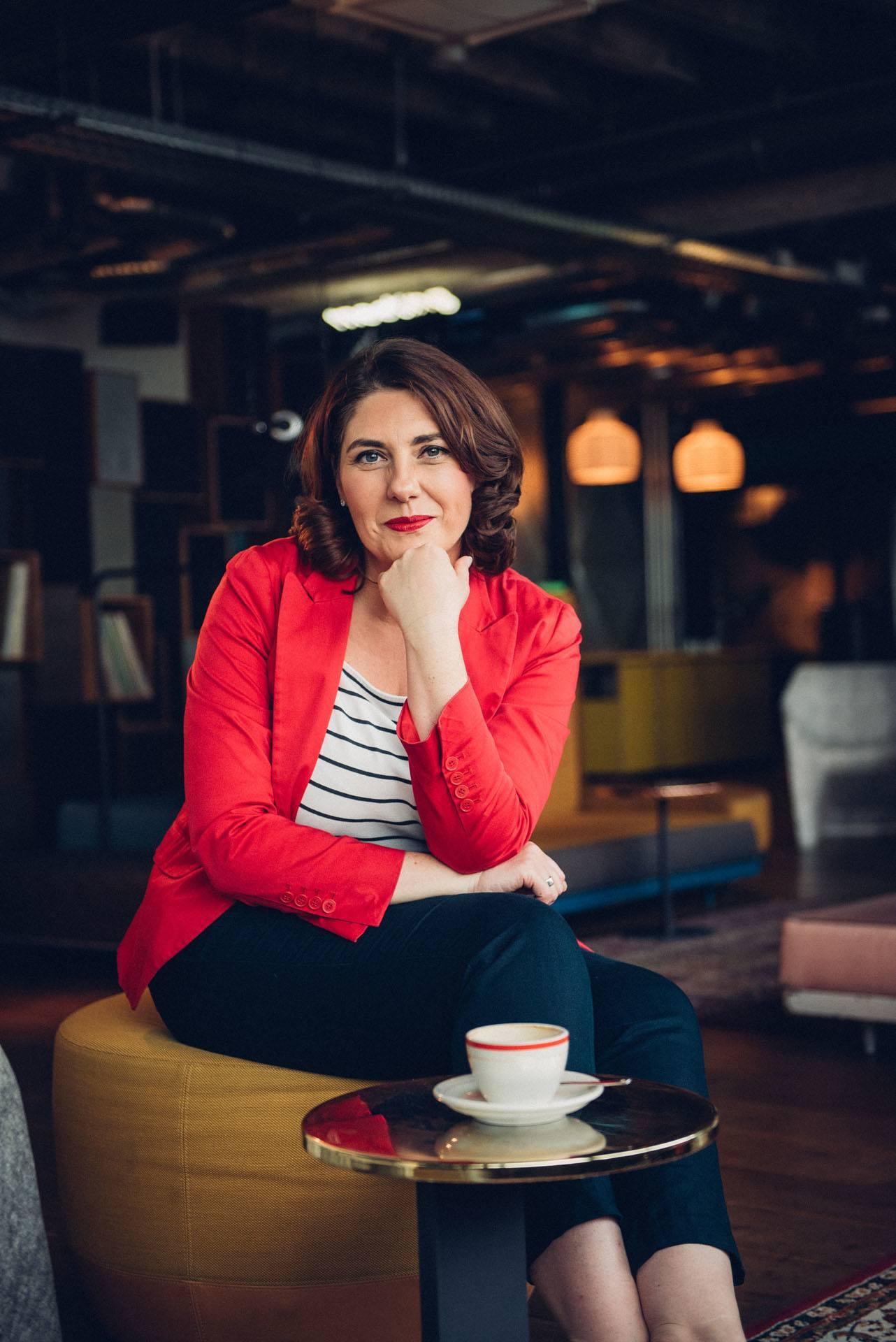 Ein weiblicher Coach mit rotem Blazer sitzt in einem Cafe und lächelt in die Kamera