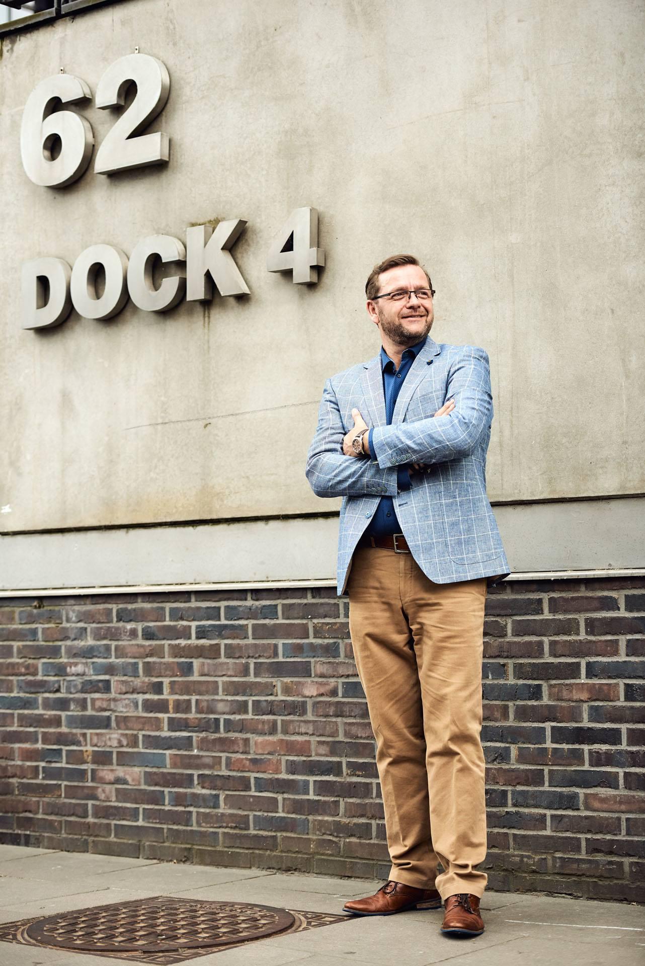 Hypnose-Therapeut im Anzug steht Portrait vor großen Buchstaben im Dock 4 im Hambuger Hafen