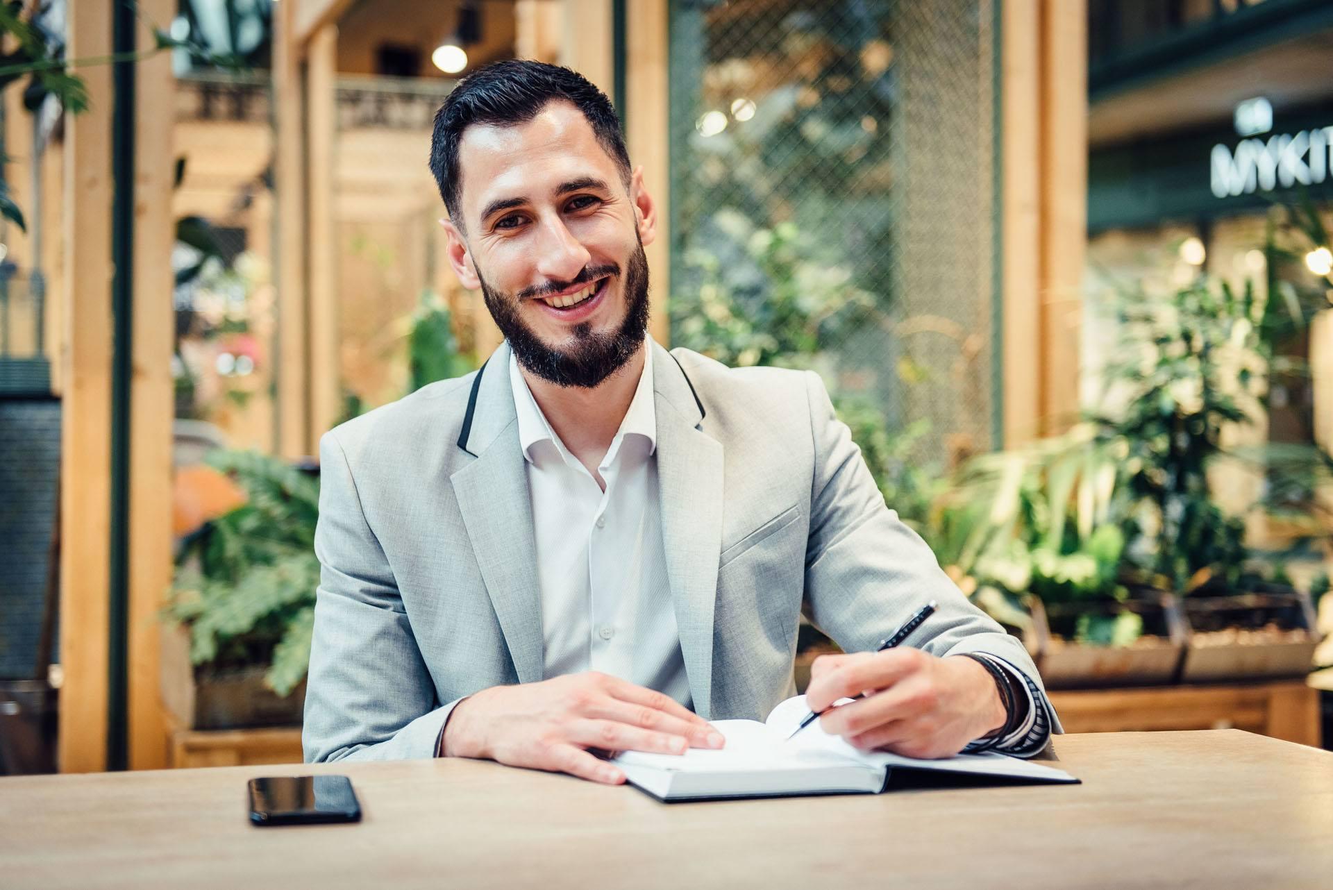 junger Mann mit Bart sitzt in einem Cafe und schreibt in sein Notizbuch