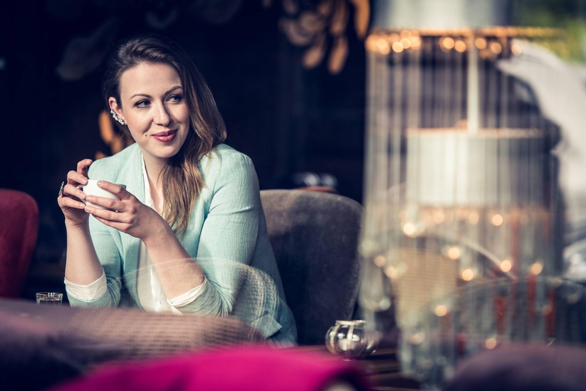 junge hübsche Frau sitzt mit Kaffeetasse hinter der Scheibe in einem Cafe und lächelt