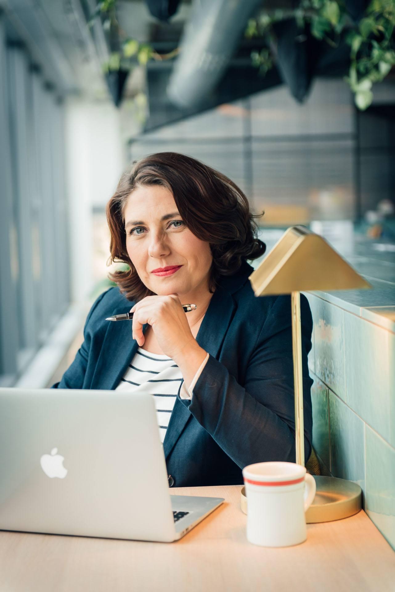 eine weibliche Coachin und Trainerin sitzt mit Laptop und Stift in einem Coworking Space