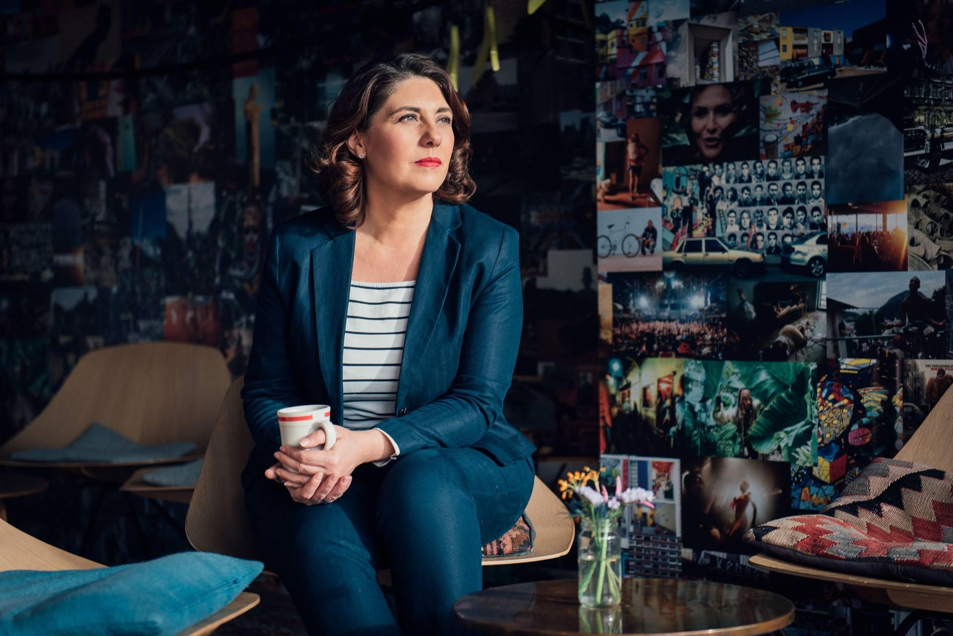 Eine Frau mit einer Kaffeetasse in der Hand sitzt vor einer bunten Wand mit vielen Bildern darauf