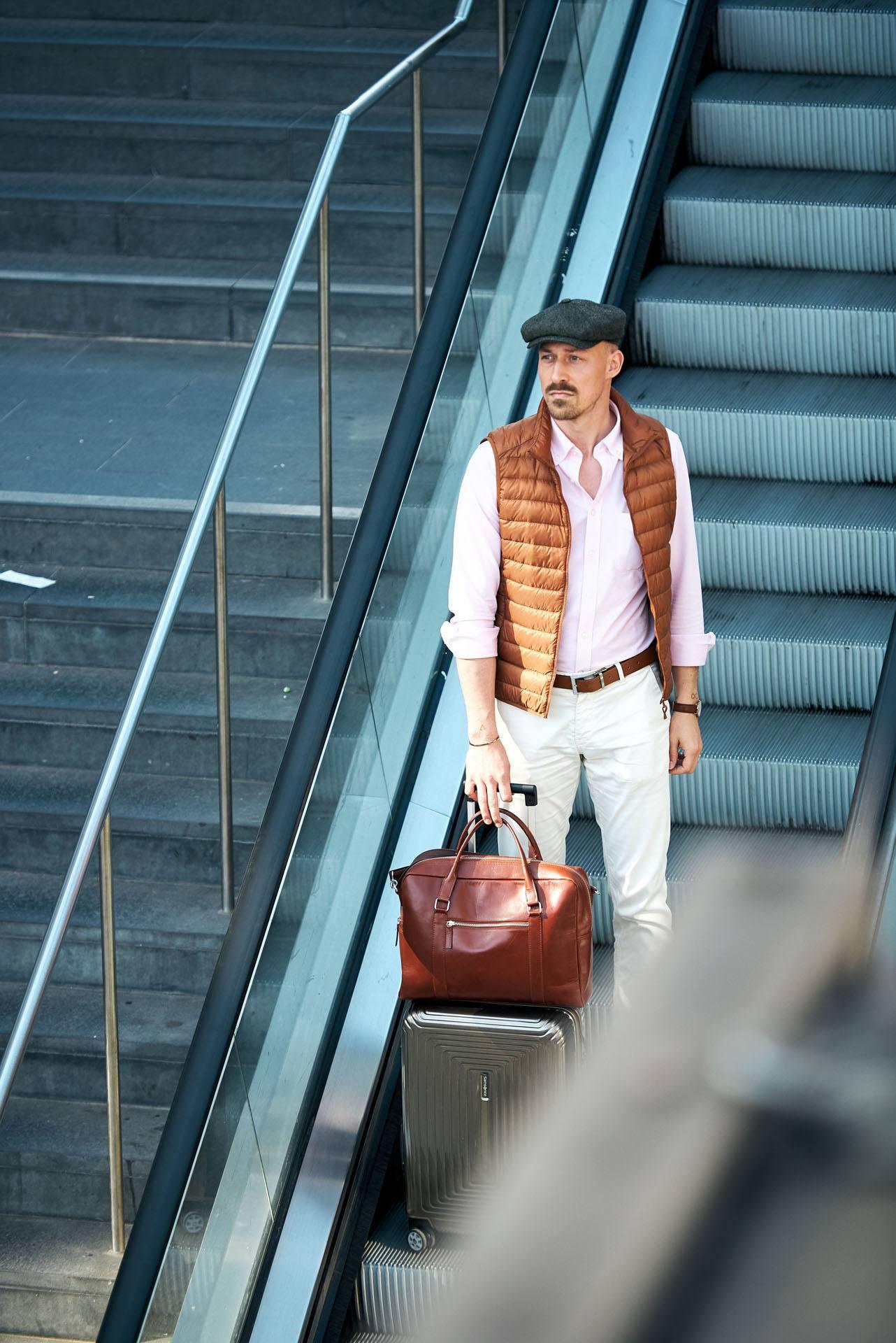 junger Mann mit Schirmmütze und Business Outfit auf einer Rolltreppe