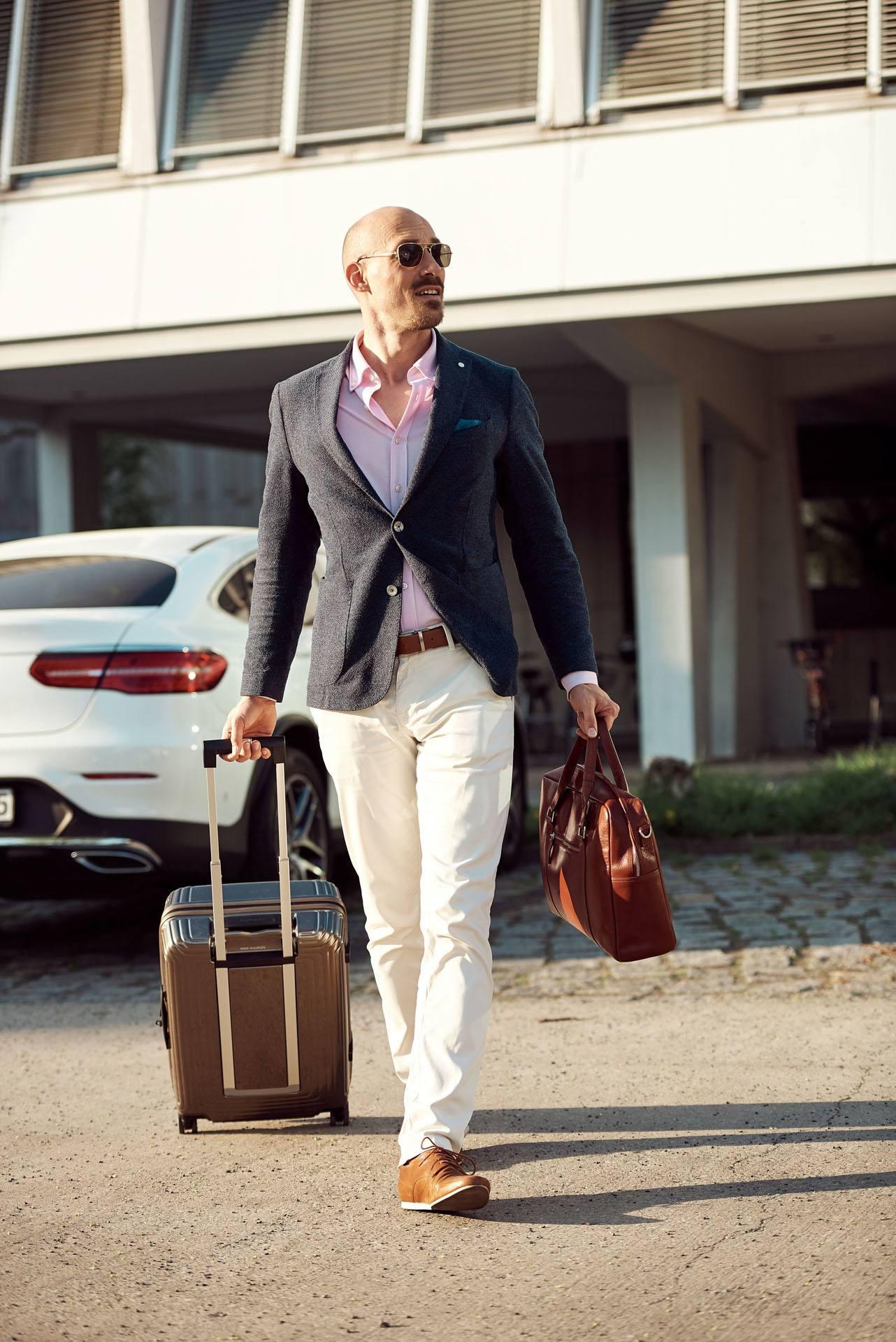 junger Mann mit Sonnenbrille, Anzug und Rollkoffer vor teurem weißen Auto