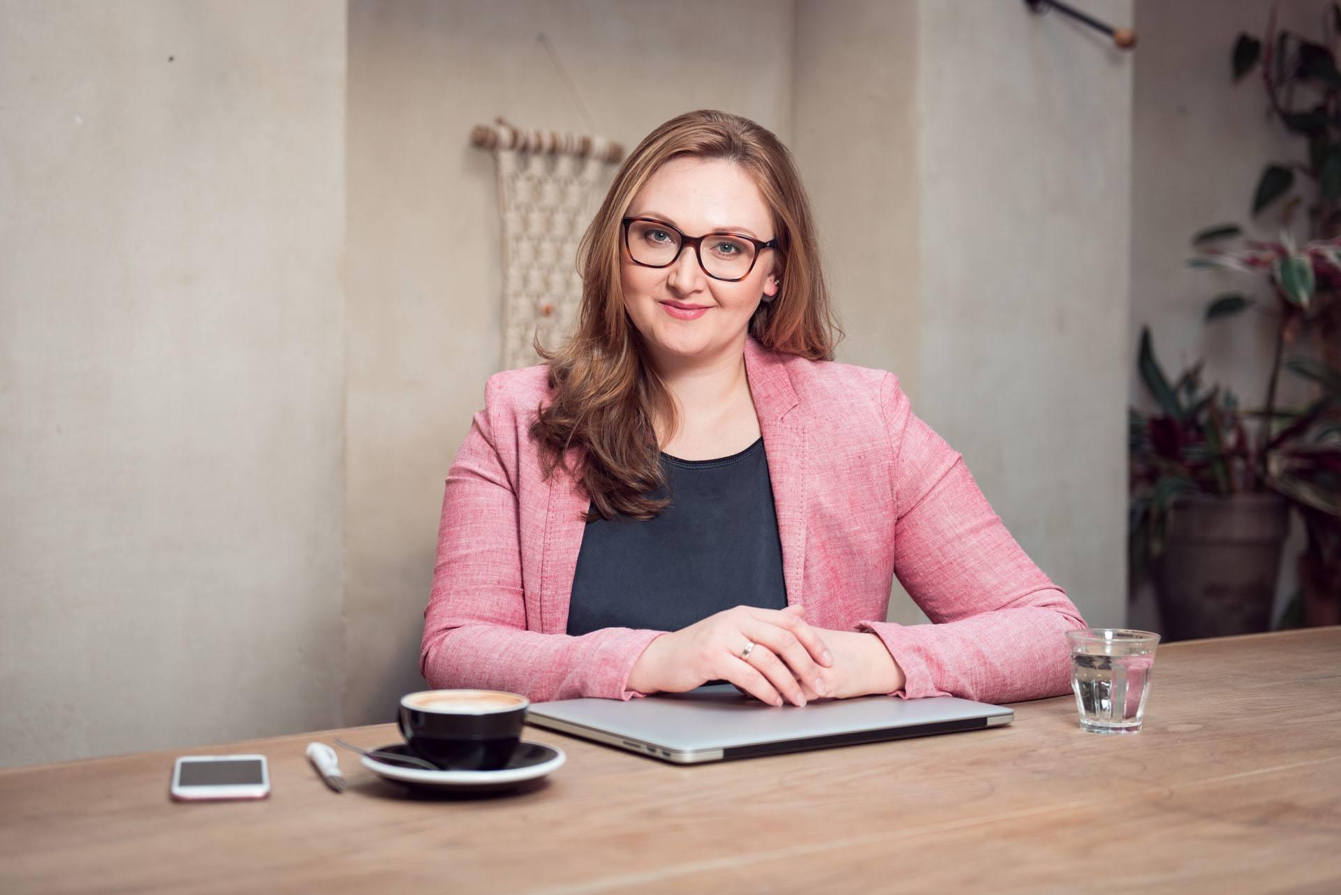 Eine junge Frau im rosa Blazer sitzt mit Laptop und Kaffeetasse in einem hippen Berliner Cafe und lächelt in die Kamera