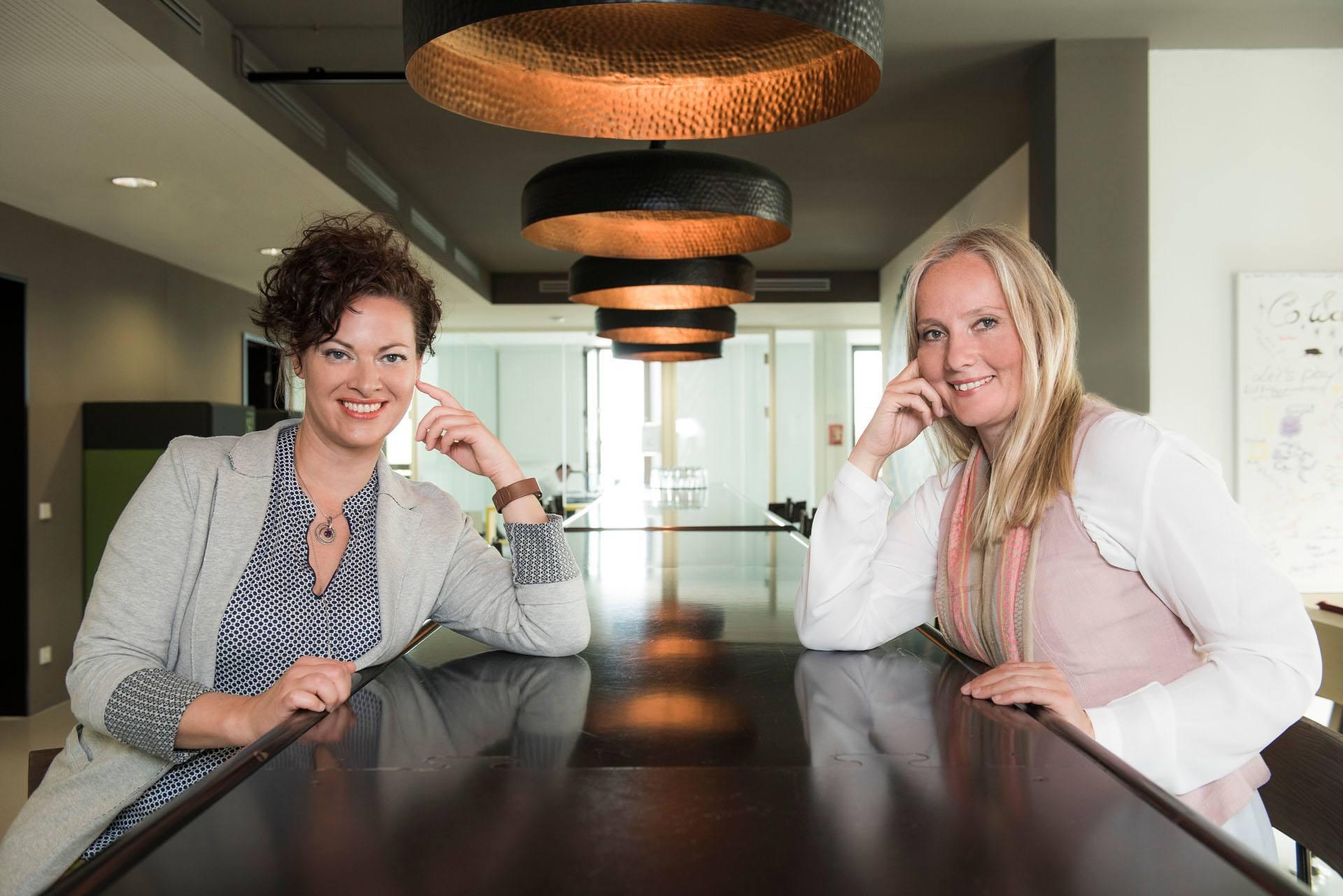 zwei weibliche Coaches und Trainerinnen sitzen an einem Tisch eines modernen Coworking-Spaces und lächeln in die Kamera