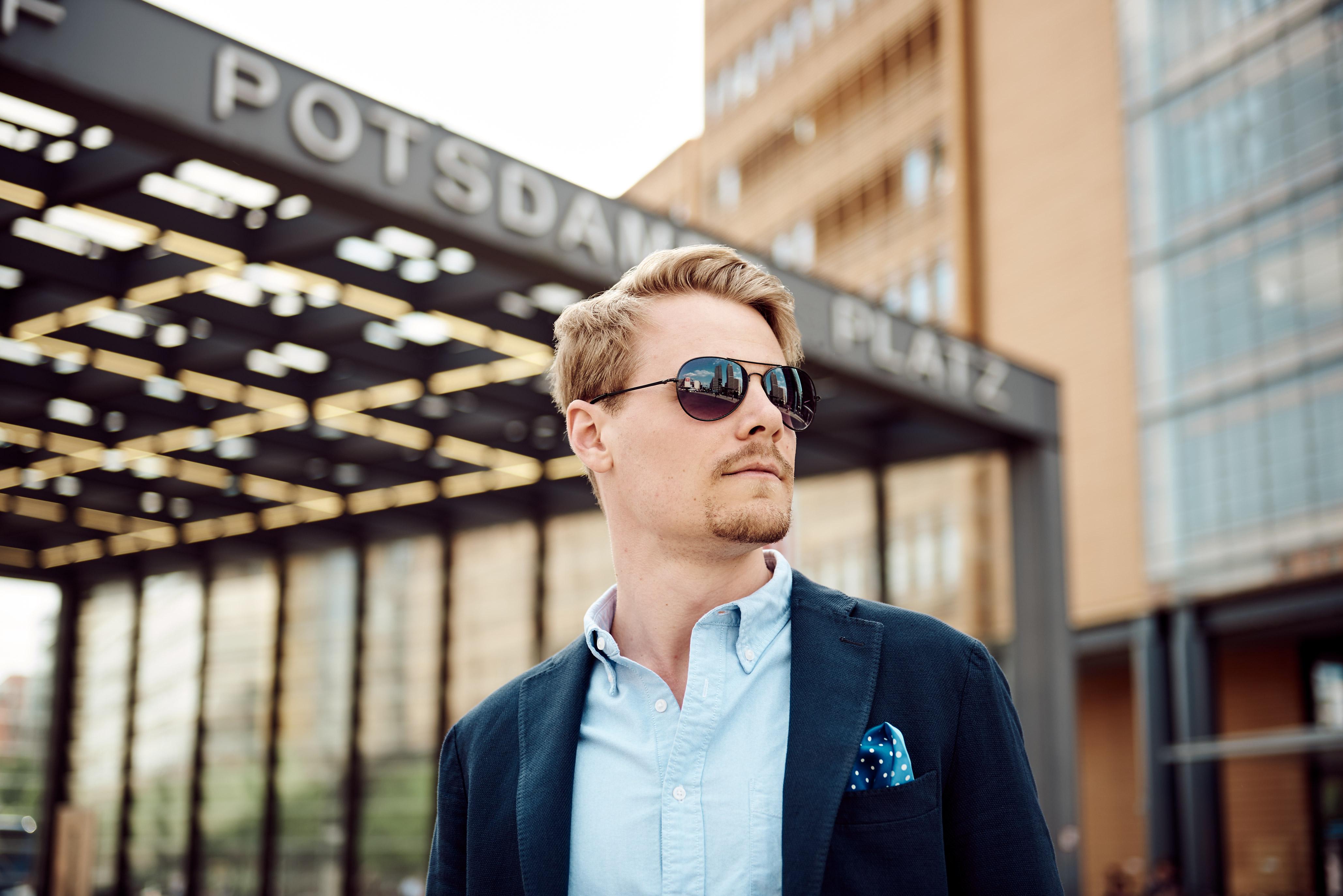 ein junger Mann mit Sportsakko, Sonnenbrille und blondem Bart schaut am Potsdamer Platz in Berlin an der Kamera vorbei