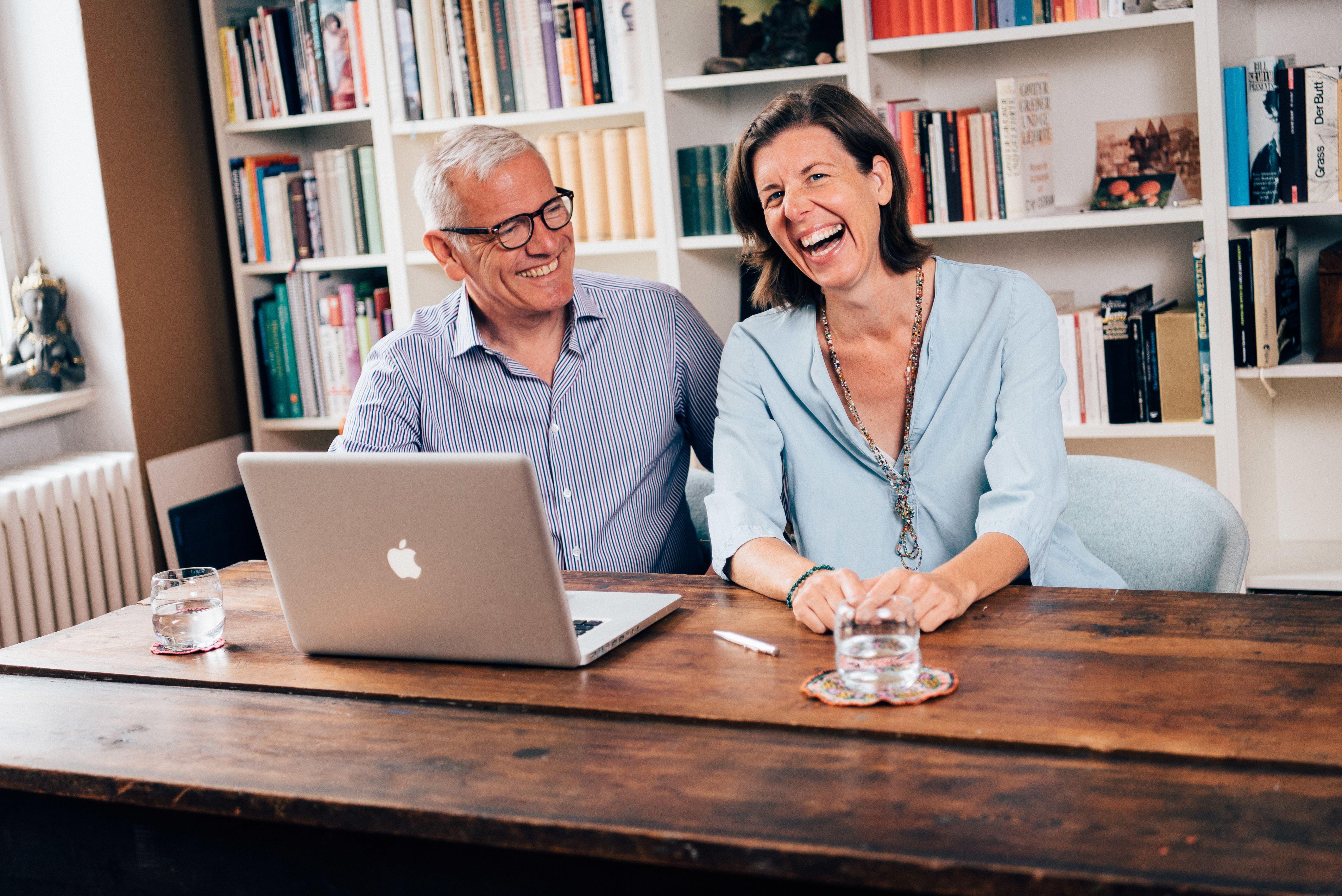 Trainer-Päarchen sitzt an einem Holztisch mit Laptop und Bücherwand und lacht in die Kamera