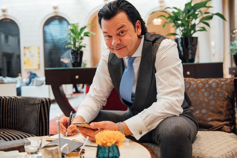 Finanzt- und Immobilientrainer im Anzug mit Smartphone und Stift in einer Hotellobby
