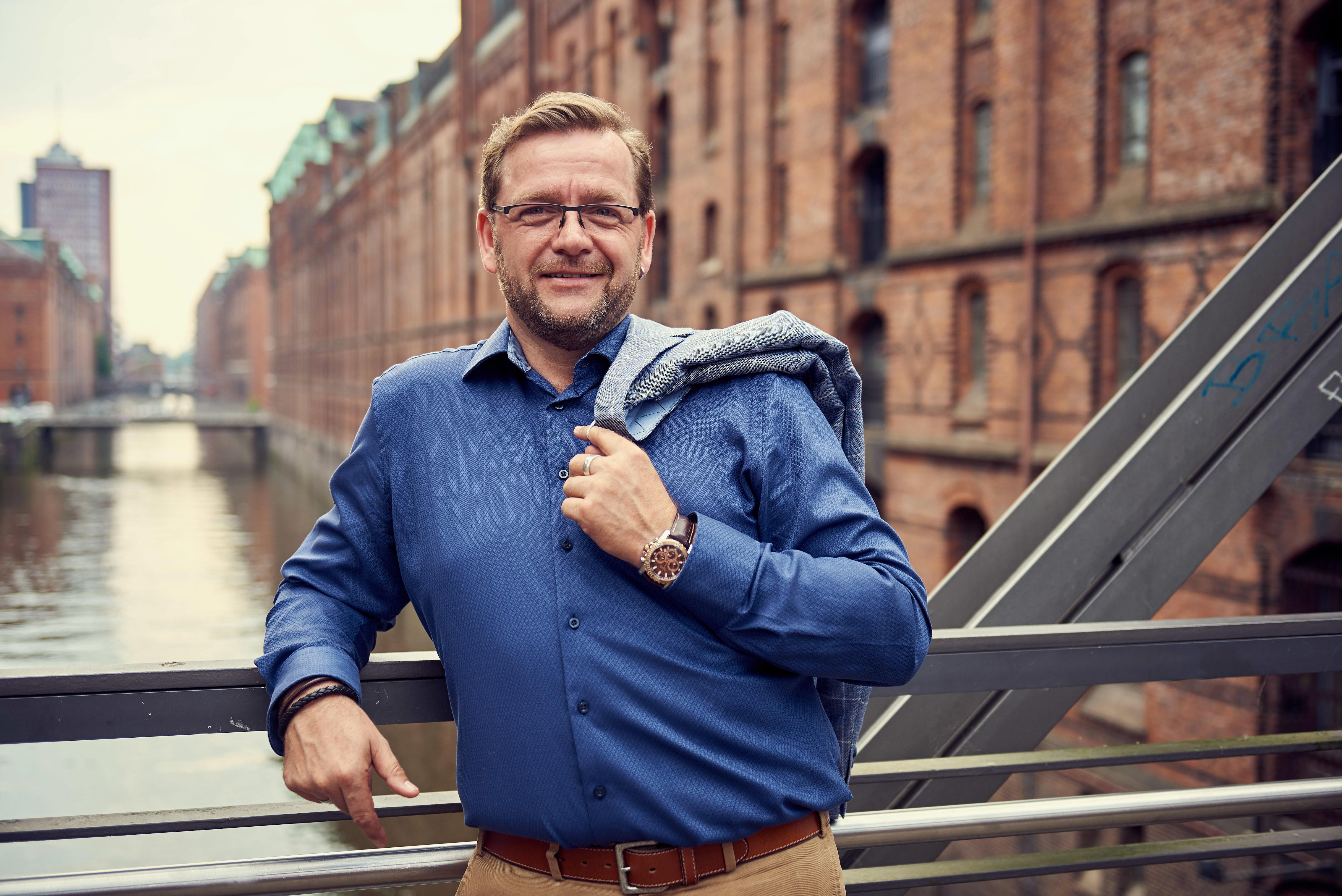 Hypnose-Therapeut wirft Sakko auf einer Brücke in der Hamburger Speicherstadt über die Schulter