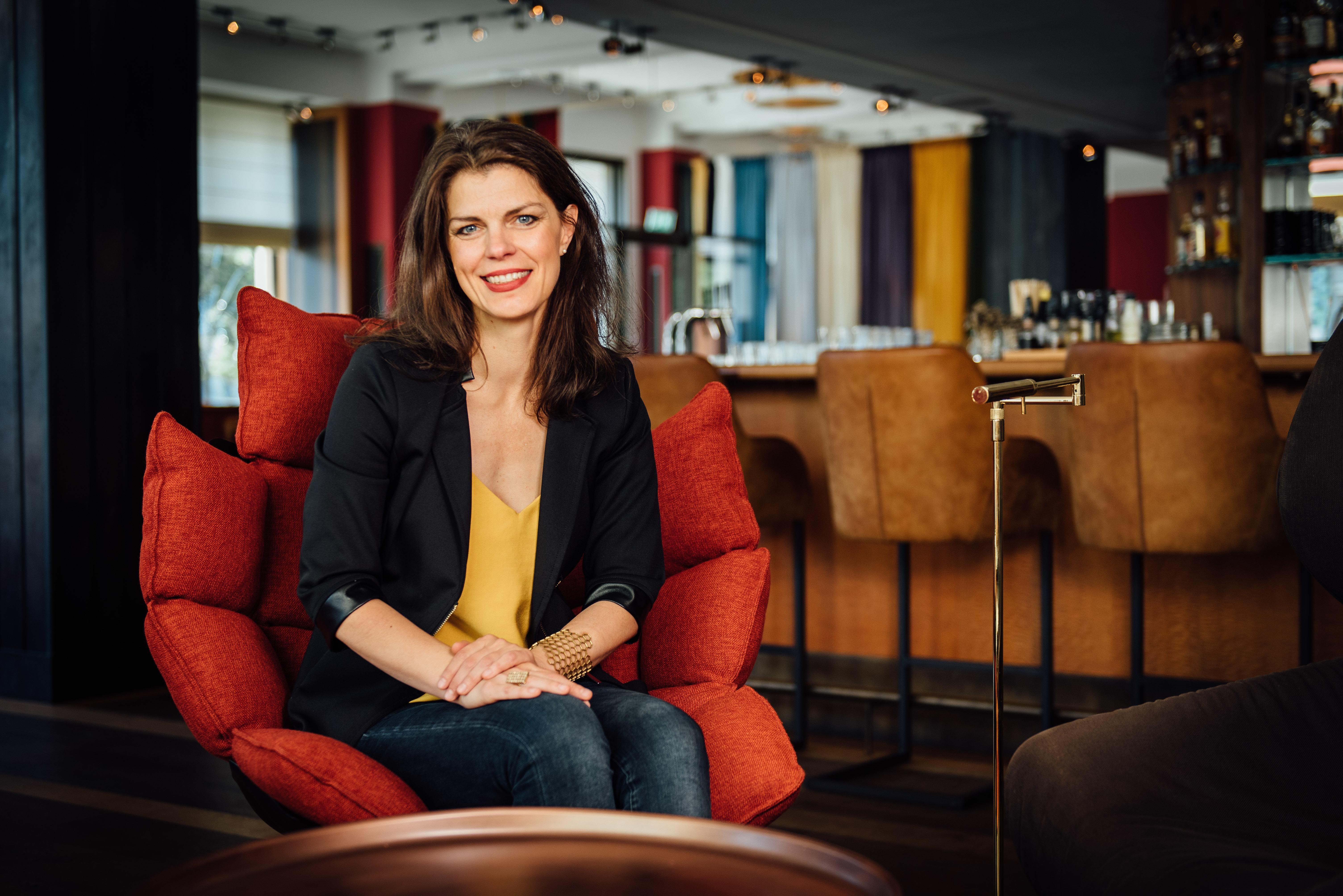 Frau auf einem roten Sessel in einer Hotel-Lobby