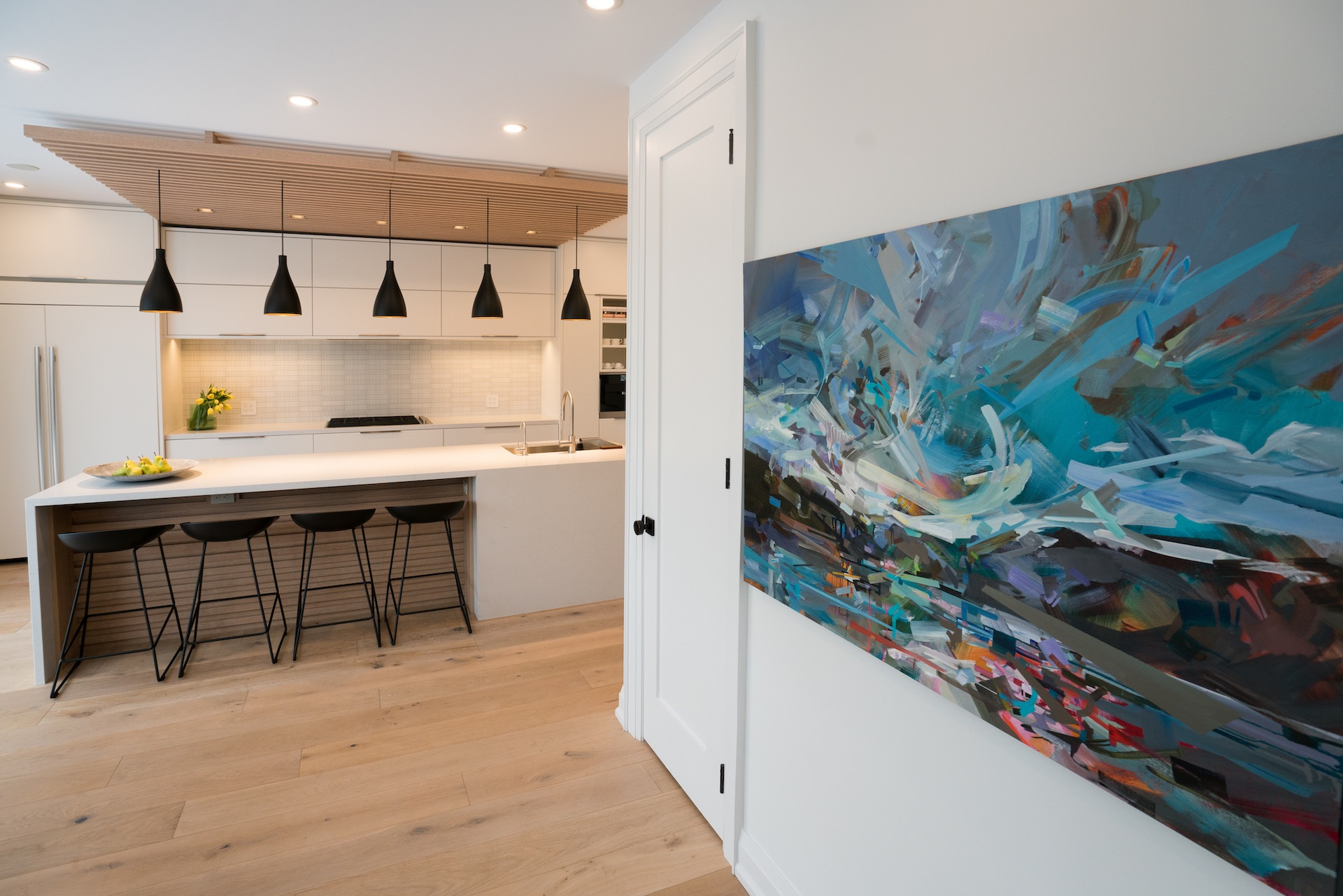Art on wall with kitchen in background