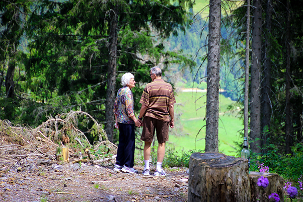 A senior couple standing in the middle of a forest, looking at each other lovingly.