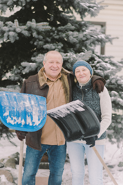 A senior couple, standing out in the snow, holding snow scrapers.