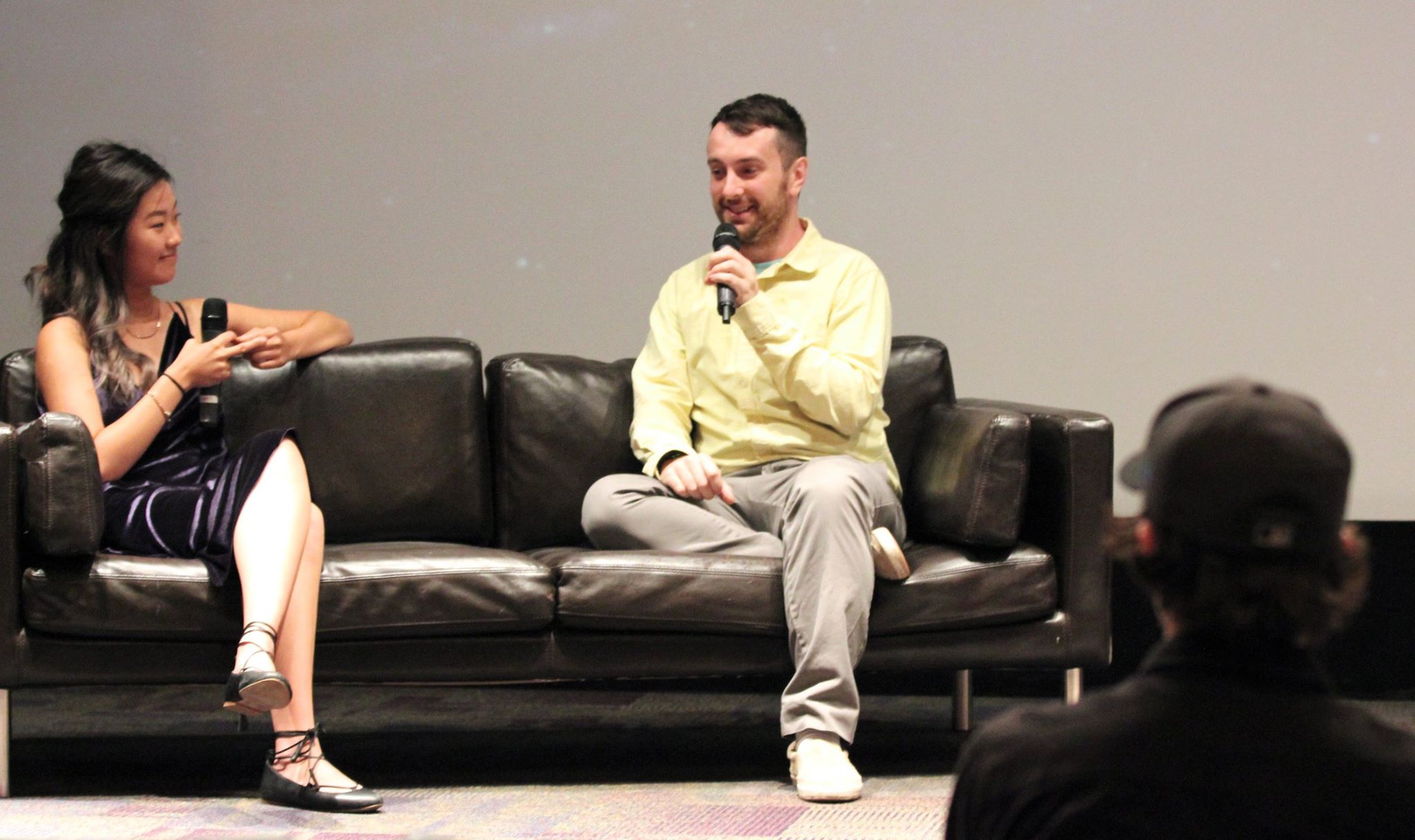 Kyle Empringham speaking at event while sitting on couch