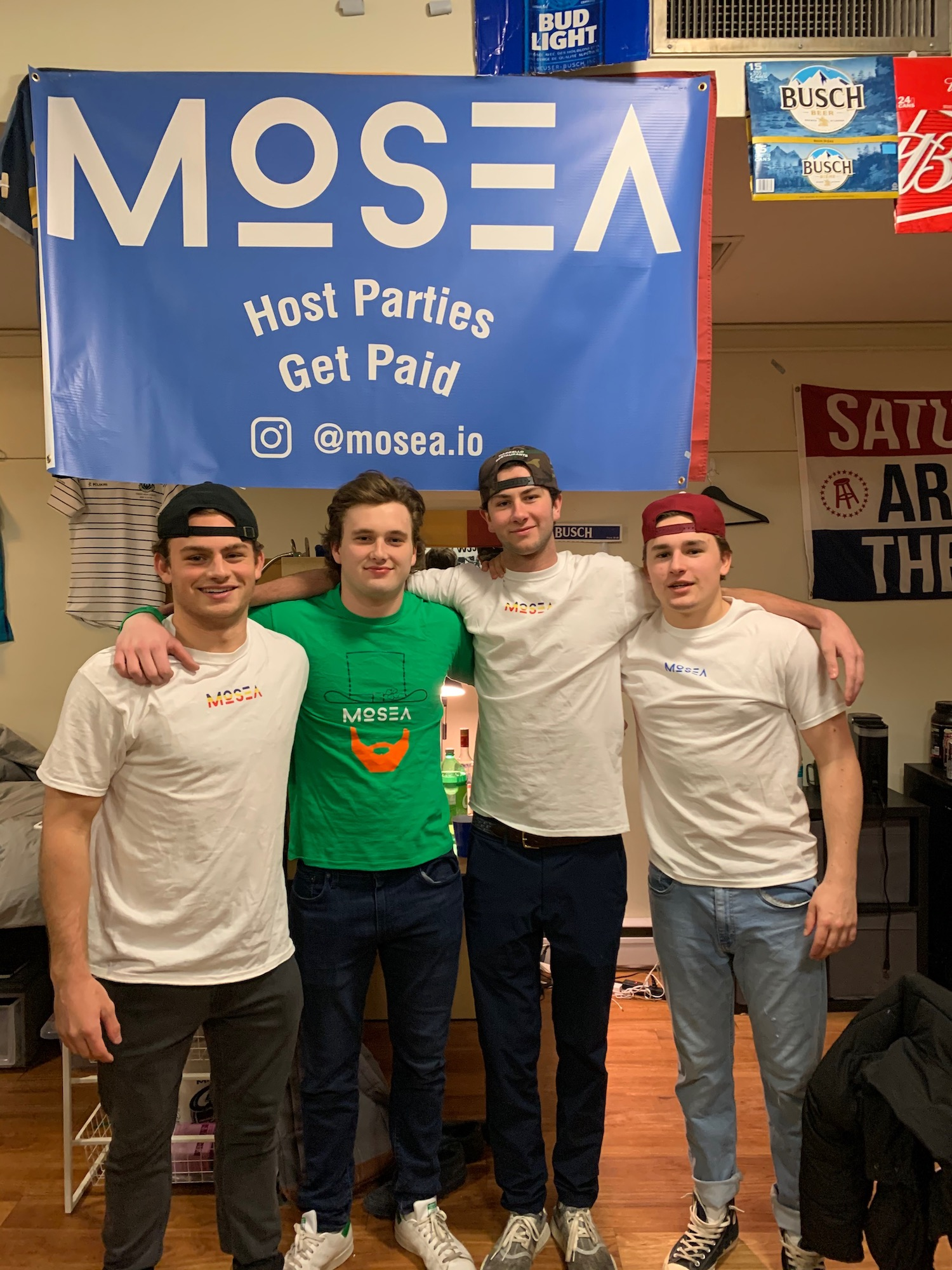Four guys in Mosea swag standing under Mosea banner