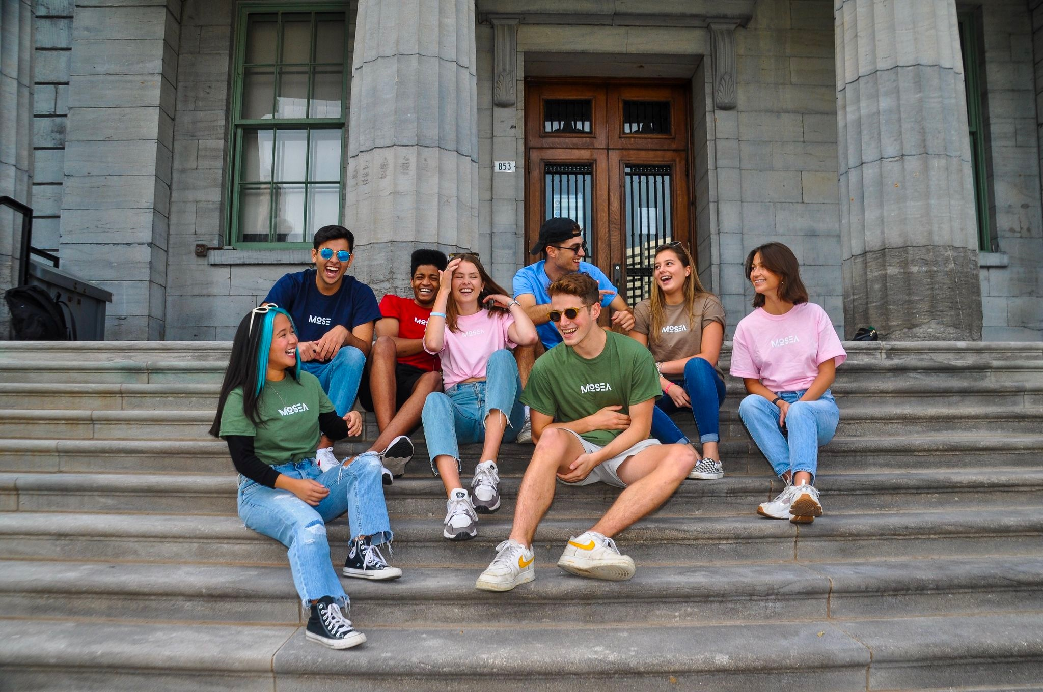 Groups of students sitting on steps wearing Mosea swag